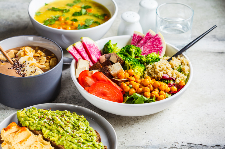bright and colorful vegan food in bowls on white countertop
