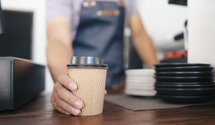 man with to go coffee in disposable cup on countertop